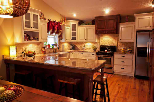 Warm and inviting Crema Bordeaux kitchen with stainless steel farm sink